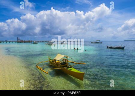 Rustic yellow fishing boat along beach on a sunny day, with impressive cloud formation above - Tropical Island of Siargao, Philippines - Stock Photo