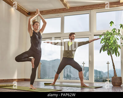 Couple practicing yoga in a room with panorama window - Stock Photo