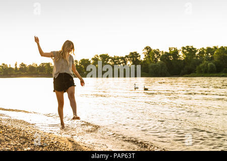 Young woman walking barefoot on riverside - Stock Photo