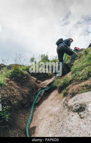 Norway, Lofoten, Man climbing Hermannsdaltinden - Stock Photo