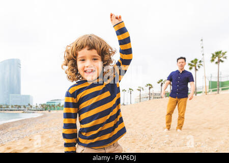 Spain, Barcelona, happy father and son on the beach - Stock Photo