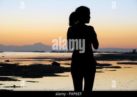 Island Woman Silhouette Profile on a Sunset Beach, Alona Beach, Philippines - Stock Photo