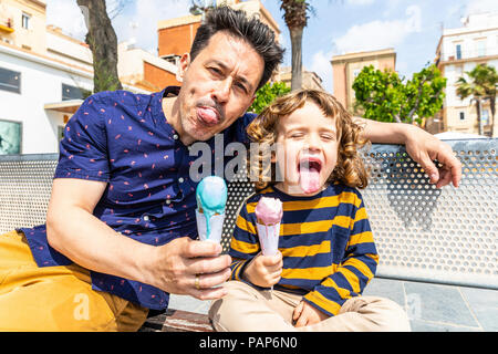 Spain, Barcelona, happy father and son sitting on bench enjoying an ice cream - Stock Photo