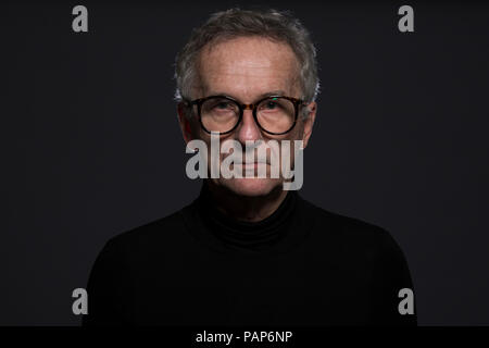 Portrait of serious senior man wearing glasses in front of dark background - Stock Photo