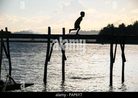 Silhouette of young boy running and playing on village island dock at sunset - General Luna, Siargao - Philippines - Stock Photo