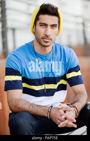 Portrait of fashionable young man wearing cap an striped t-shirt - Stock Photo