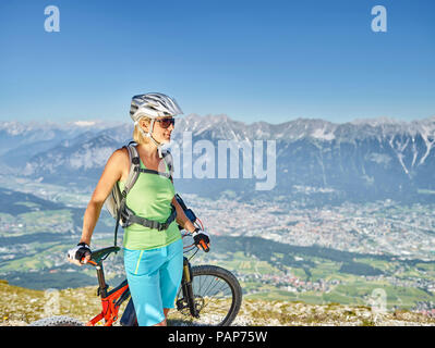 Austria, Tyrol, Woman mountain biking at Patscherkofel, Innsbruck in background - Stock Photo