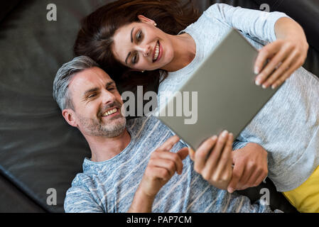 Happy couple lying on couch at home sharing a tablet - Stock Photo