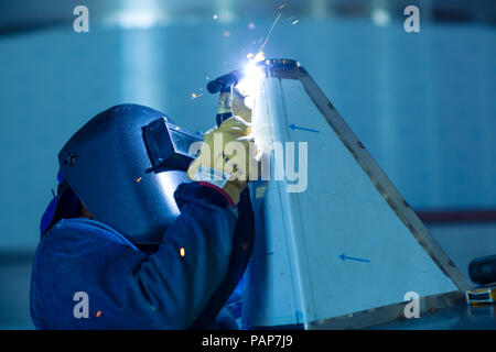 Welder in industrial plant welding tanks - Stock Photo