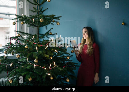 Smiling woman with tablet standing besides decorated Christmas tree - Stock Photo