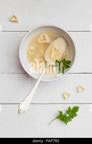 Silver spoon in bowl of chicken soup with heart-shaped noodles and parsley - Stock Photo