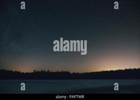 Sweden, Sodermanland, frozen lake Navsjon in winter under starry sky at night - Stock Photo