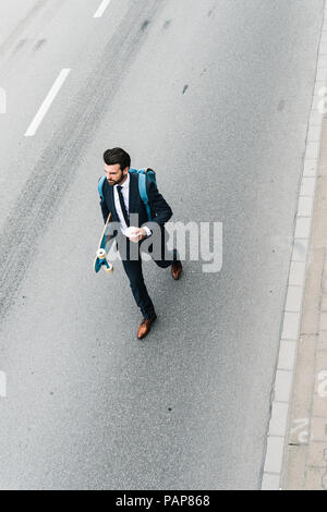 Businessman with takeaway coffee and skateboard walking on the street - Stock Photo