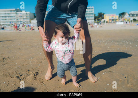 France, La Baule, baby girl learning to walk with her father on the beach - Stock Photo