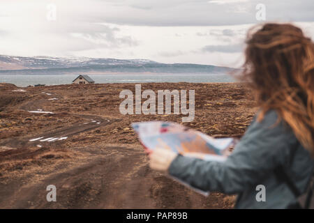 Iceland, woman with map in  landscape with single house - Stock Photo