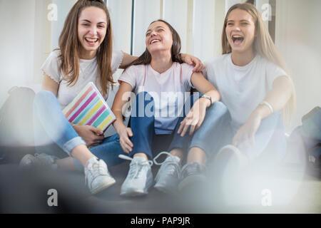 Happy teenage girls sitting on floor in school - Stock Photo