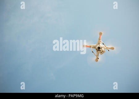 Drone flying in blue sky - Stock Photo
