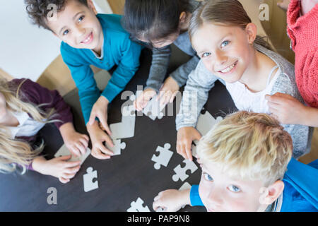 Portrait of smiling pupils playing jigsaw puzzle in school together - Stock Photo