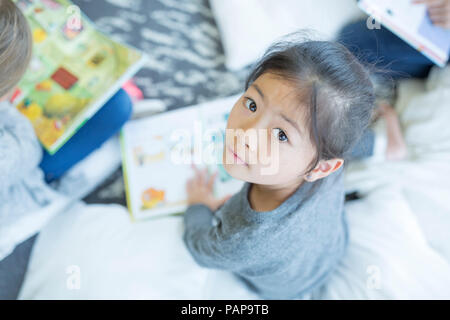 Portrait of schoolgirl sitting on the floor with book in school - Stock Photo