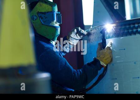 Welder in industrial plant welding tanks - Stock Photo