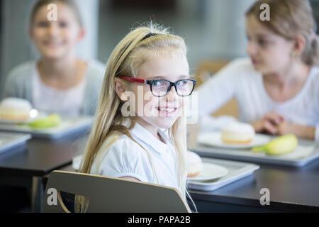 Portrait of smiling schoolgirl with classmates in school canteen - Stock Photo