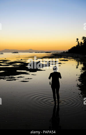 Woman Standing in Shallow sea water at low tide, taking photos with ripples at her feet - - Alona Beach, Bohol - Philippines - Stock Photo