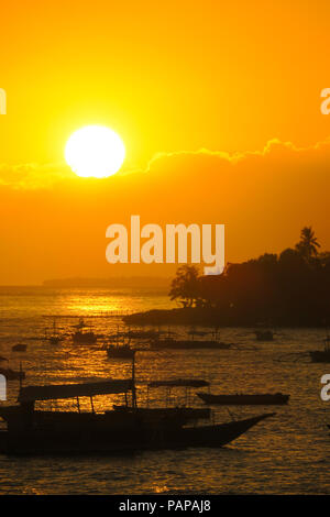 Large, Golden sun about to dip below the clouds above the fishing boats on Alona Beach, Philippines - Stock Photo