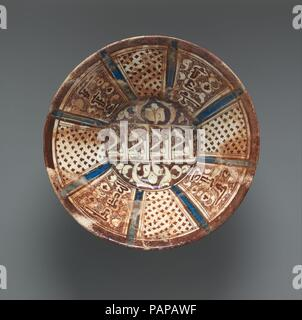 Ceramic Bowl. Dimensions: H. 4 11/16 in. (11.9 cm)  Diam. 9 1/4 in. (23.5 cm)  Wt. 18.8 oz. (533 g). Date: 12th century.  Bowls such as this one were typical tableware used daily by well-to-do, middle-class owners for liquid or solid food. This example's biconical shape with a high, slightly conical foot was common in ceramics during the twelfth and thirteenth centuries in both the eastern and the western spheres of the Seljuq realm. Its decorative elements, formulaic benedictory inscriptions--baraka kamila (consummate blessing) in radiating panels, and al-'izz (glory) repeated four times in r - Stock Photo