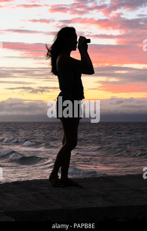 Young Woman Silhouette Profile, Taking Pictures of a stunning pink island sunset - Bohol, Philippines - Stock Photo
