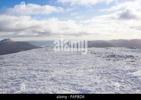 Climber on top of Scottish Mountain Ben Vorlick During Winter - Stock Photo