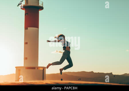 Young woman jumping in desert landscape at lighthouse - Stock Photo