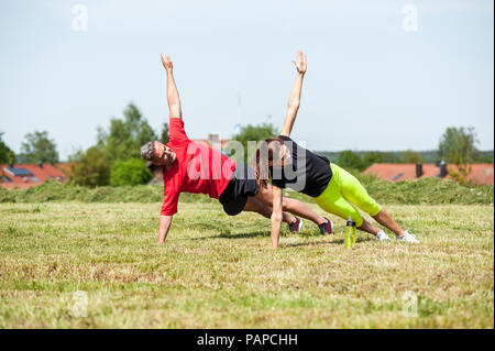 Couple doing side plank exercise on meadow - Stock Photo