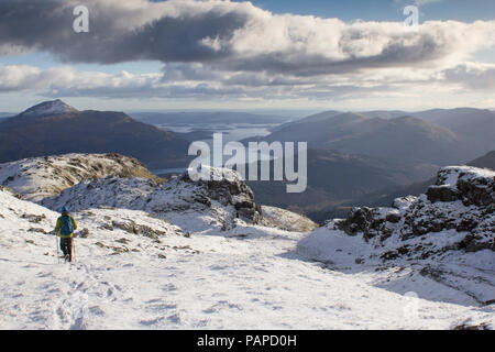 A Climber climbing the snow covered mountain Ben Vorlick during winter with Ben Lomond and the Trossachs mountain range in view. Scotland. - Stock Photo