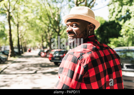 Cool young man walking in the city, portrait - Stock Photo