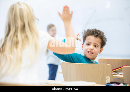 Pupils high fiving in class - Stock Photo