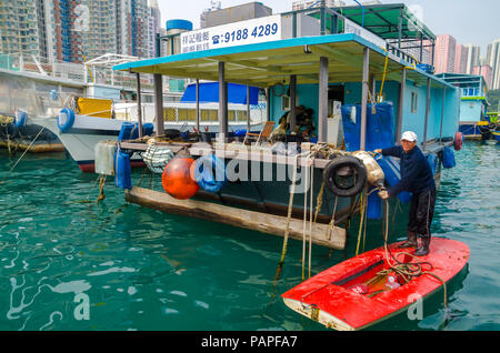 A man is doing daily chores in his floating house in Aberdeen floating village in Hong Kong - Stock Photo