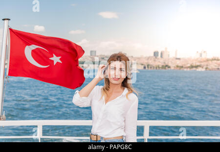 Beautiful woman travels with ferry between Asia and Europe with view of Turkish flag.Istanbul,Turkey - Stock Photo