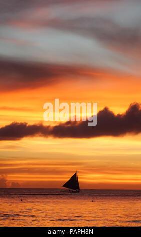 Sailboat silhouette under a dramatic, cloudy orange island sunset  - Boracay, Aklan - Philippines - Stock Photo