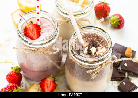 Set of milkshake in jars. Banana chocolate and strawberry milkshakes with nuts and coconut. Summer dessert. Healthy food. - Stock Photo