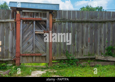 Old rustic wooden gate in natural village fence. Countryside rural scene, agrotourism - Stock Photo
