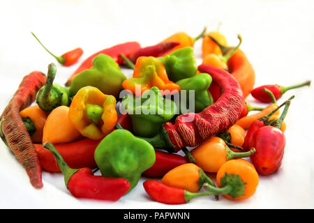 Small spicy chili peppers of different colours on white background - Stock Photo