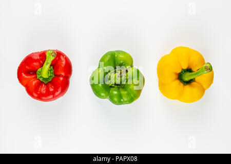 Top view of three fresh bright bell peppers on white background. Shot from above of green, yellow and red paprika vegetables - Stock Photo