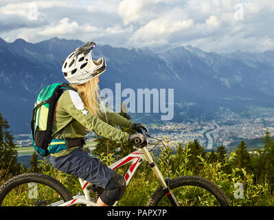 Austria, Tyrol, female downhill mountain biker looking into valley - Stock Photo