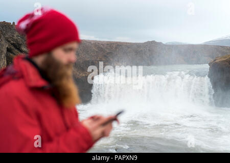 Iceland, North of Iceland, young man using smartphone, waterfall in the background - Stock Photo