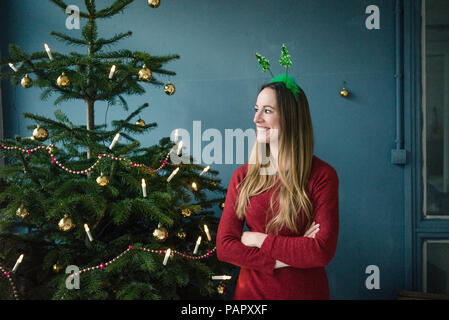 Content woman with Christmas headdress standing besides decorated Christmas tree - Stock Photo