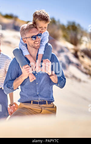 Happy father carrying son on shoulder at the beach - Stock Photo