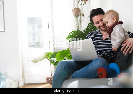 father sitting on couch with his little daughter, using laptop - Stock Photo