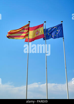 Official flags of Catalonia, Spain and The European Union (EU) waving on a blue sky. - Stock Photo