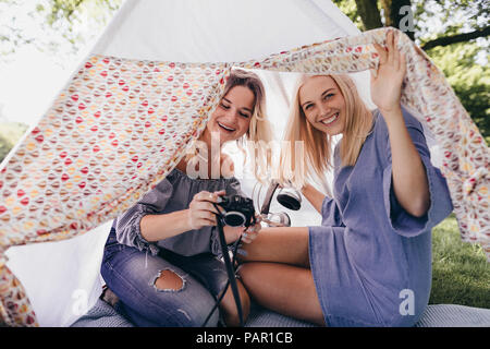 Two happy young women with old-fashioned camera in a teepee in a park - Stock Photo