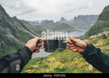 Norway, Lofoten, Moskenesoy, Two people toasting with tin cups - Stock Photo